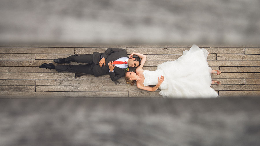 wedding couple laying on ground for an award winning photo