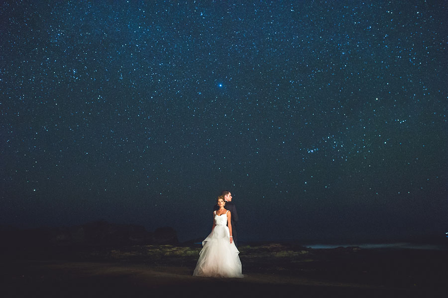 bride and groom at night with the stars in the background