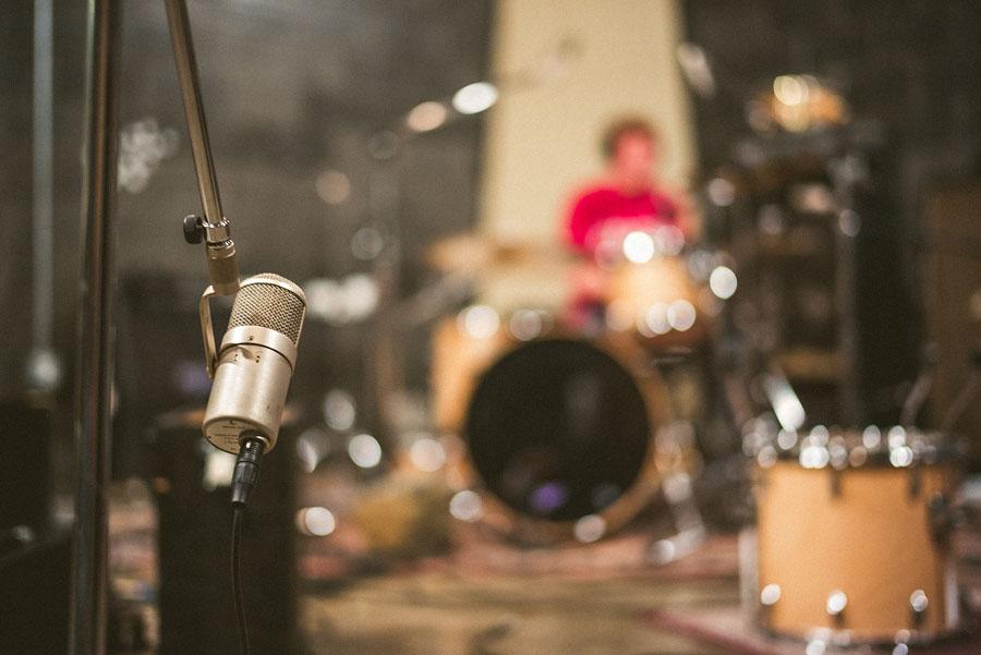Drummer recording drum tracks in a studio