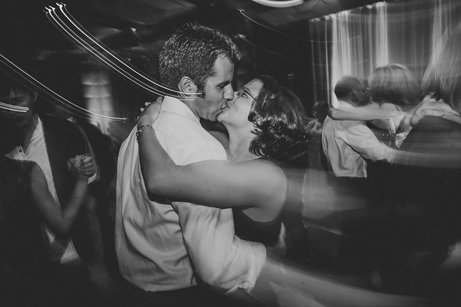 man and woman kissing while dancing at reception