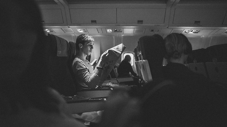 guy in airplane reading paper