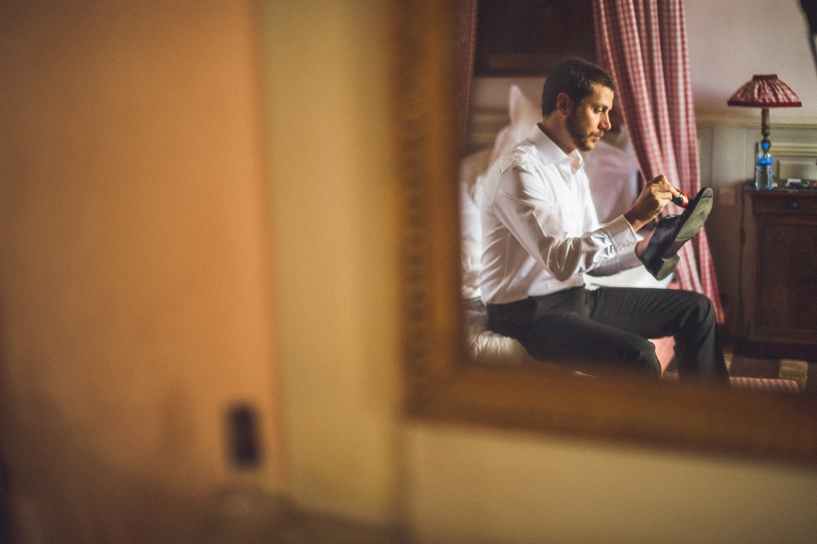 groomsmen cleaning shoes while getting ready