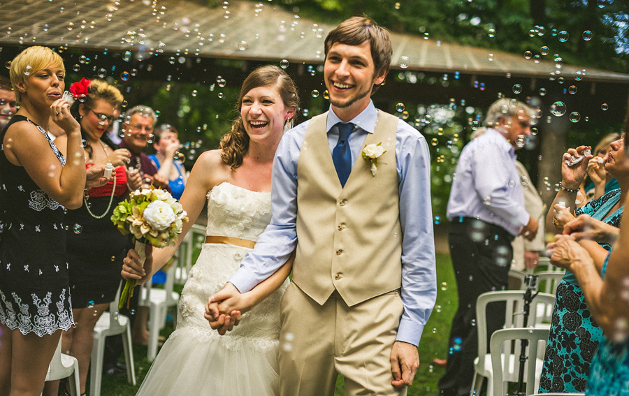 bride and groom leaving ceremony with bubbles