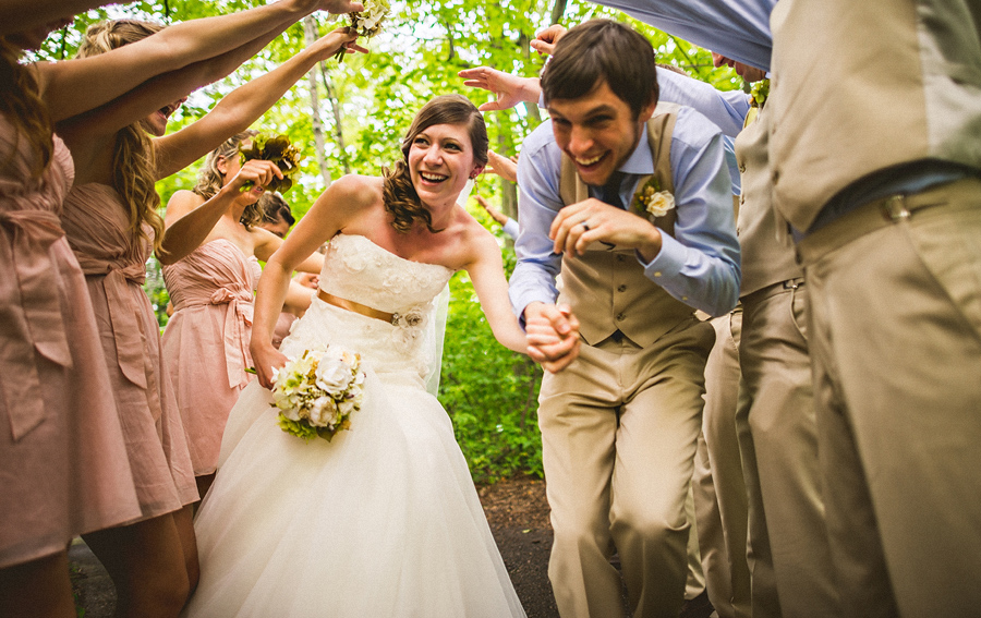 bride and groom running underneath people at exit