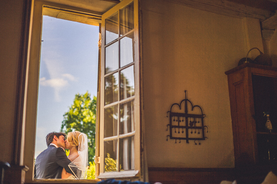 window photo of french groom and american bride