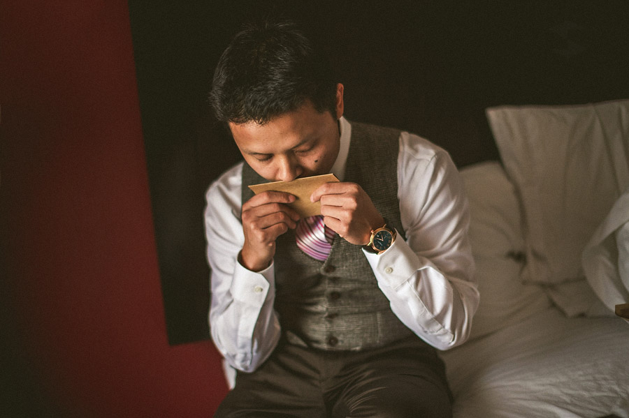 groom with letter from bride getting ready