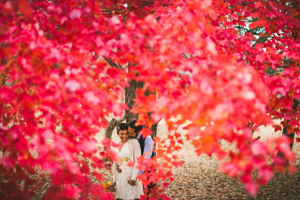 bride and groom through the fall leaves of baltimore