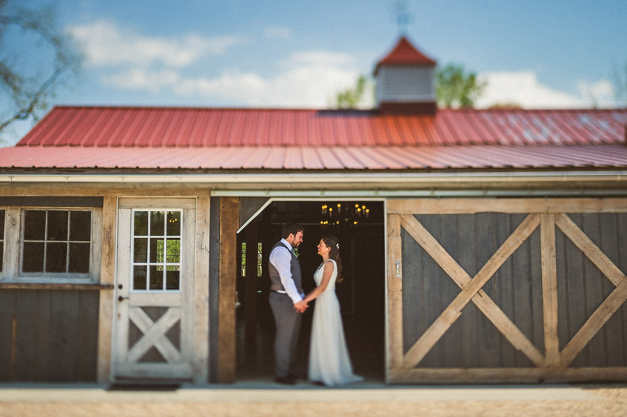 bride and groom standing in barn