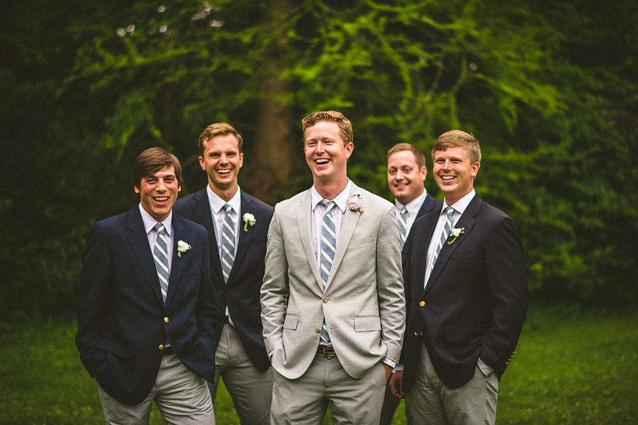 groom with groomsmen laughing outdoors