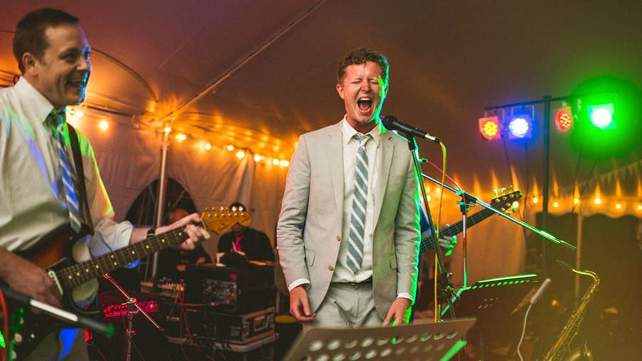 groom singing on stage with wedding band