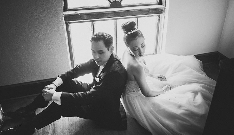dramatic quiet moment of bride and groom sitting together after their wedding