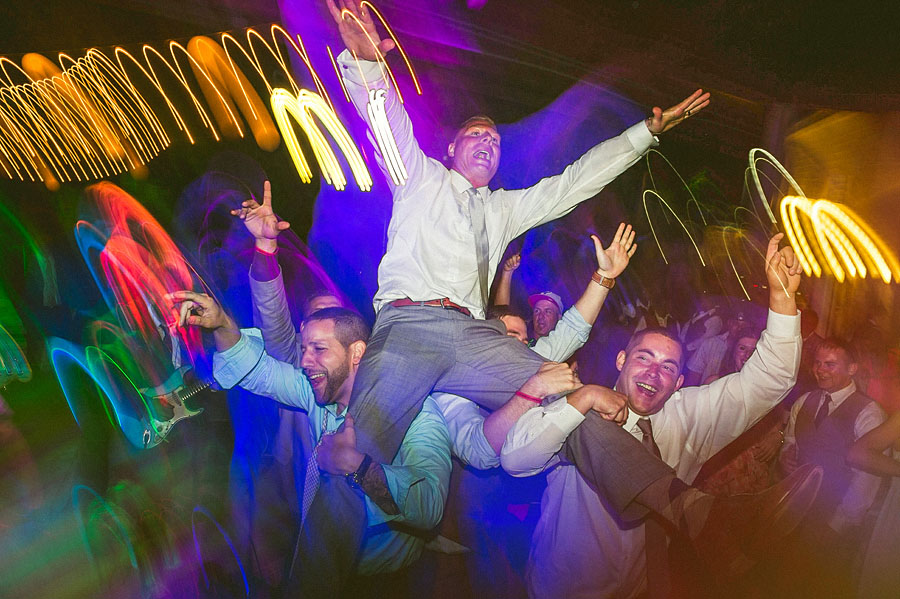 guys holding groom up while dancing