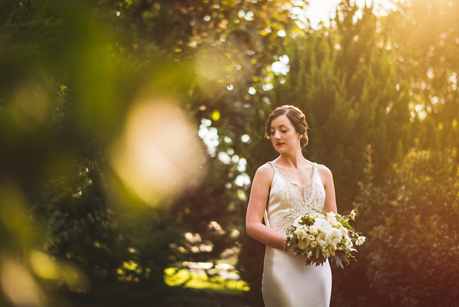 bridal portrait in trees with sun flare