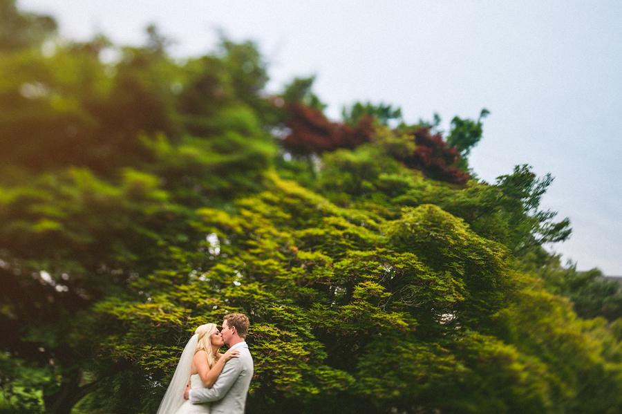 tilt shift portrait of the bride and groom kissing